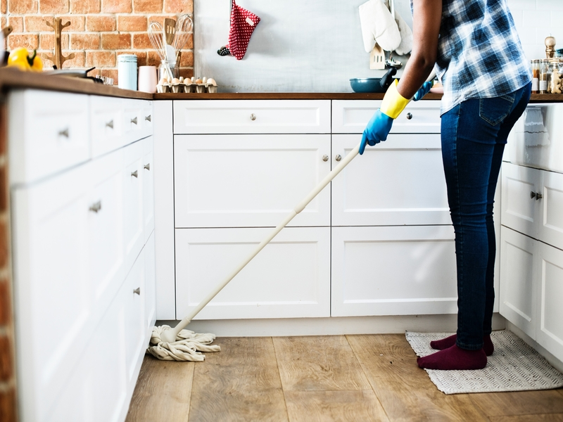 Person mopping the floor in the kitchen