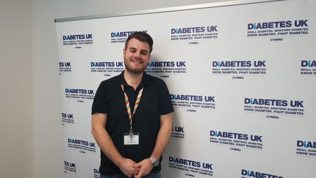 Josh James who works for the Diabetes UK stands in front of a a backdrop showing the charity's logo.