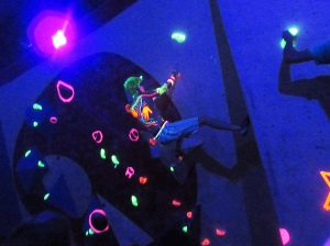 A climber tackles the neon holds in darkness.