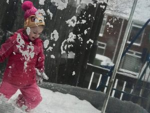 A young girl plays on a trampoline in the snow